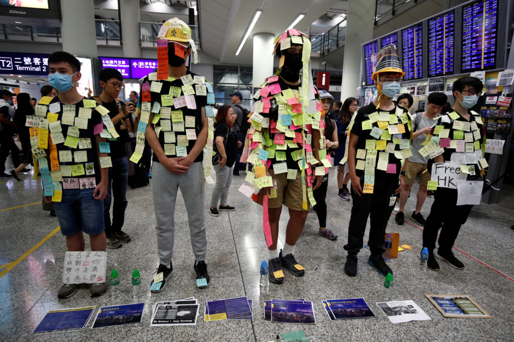 "Demonstrators wear post-it notes as part of the ""Lennon Wall"" movement during a protest against the recent violence in Yuen Long, at Hong Kong airport, on July 26, 2019. Photo by Edgar Su/Reuters"