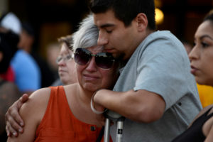 Justin Bates, a survivor of the Gilroy Garlic Festival mass shooting, and his mother, Lisa Barth, attend a vigil outside of Gilroy City Hall, in Gilroy, California, U.S. July 29, 2019. Picture taken July 29, 2019. While attending the festival, Bates was shot through the leg and grazed with numerous bullets while trying to help his friends escape the massacre. Photo by Kate Munsch/Reuters