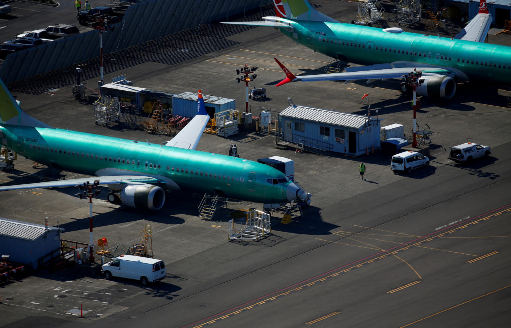 A worker walks past unpainted Boeing 737 MAX aircraft seen parked in an aerial photo at Renton Municipal Airport near the Boeing Renton facility in Renton, Washington, U.S. July 1, 2019. Picture taken July 1, 2019. Photo by: Lindsey Wasson/Reuters