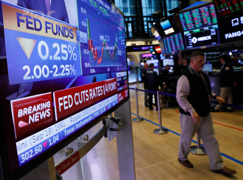 A screen displays the U.S. Federal Reserve interest rates announcement as traders work on the floor of the New York Stock ...
