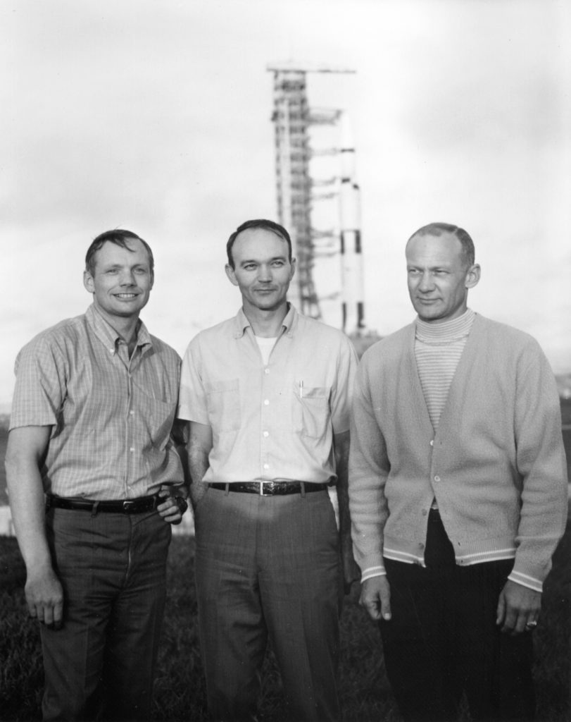 Neil Armstrong (left), Mike Collins, and Buzz Aldrin pose with the Saturn V in the background on May 20, 1969. Photo by NASA