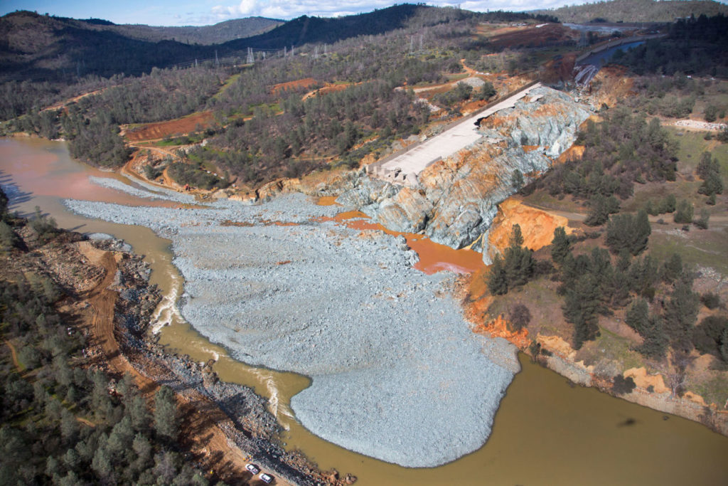 An aerial view of the damaged Oroville Dam spillway in California, and the debris field just below, in February 2017. Photo by California Department of Water Resources