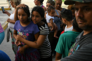 Asylum seekers line up for a meal provided by volunteers as they wait in hopes of being let through the nearby U.S. port of entry in a makeshift migrant camp near the Gateway International Bridge in Matamoros, Tamaulipas, Mexico, June 29, 2019. REUTERS/Loren Elliott - RC17E8349C10
