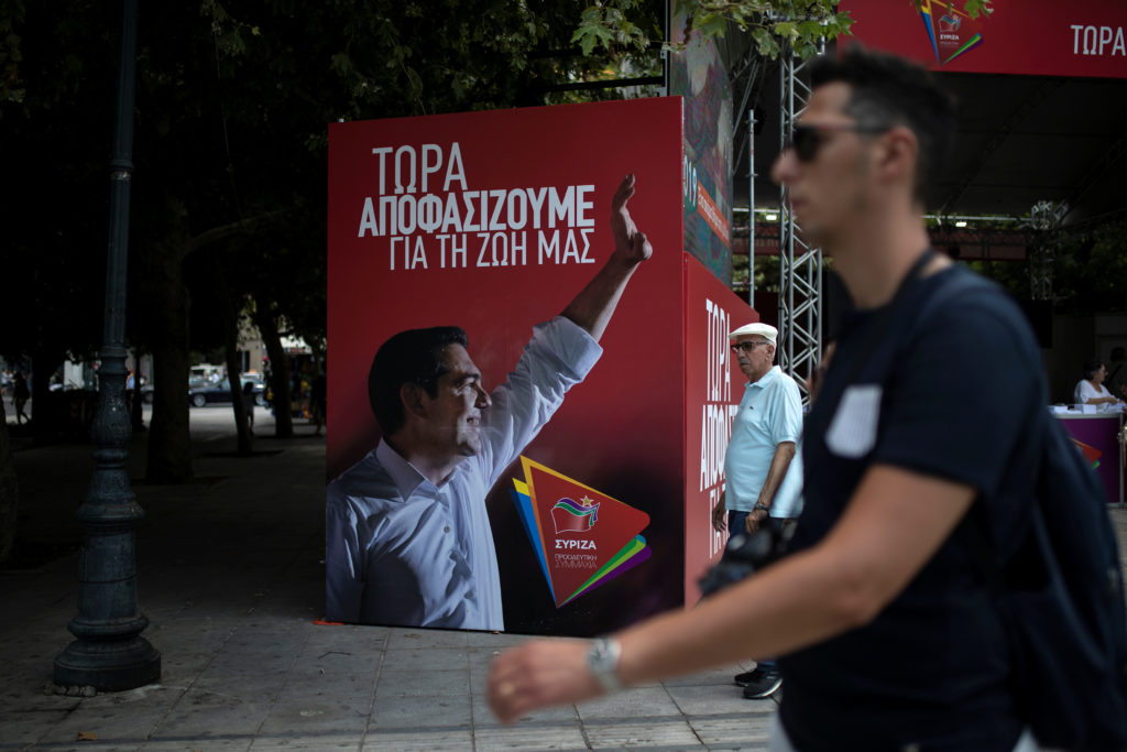 "People walk past a poster depicting Greek Prime Minister Alexis Tsipras at the election kiosk of the leftist Syriza party in Athens, Greece, July 6, 2019. The slogan on the poster reads ""Now we decide for our lives"". Photo by Alkis Konstantinidis/Reuters"