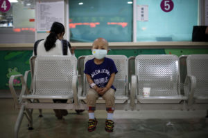 Four-year-old Niuniu, who has late-stage neuroblastoma, a malignant cancer of the nervous system, sits on a bench while his mother pays his medical bills after getting tested for his fifth round of chemotherapy at Shanghai Children's Hospital May 2, 2013. China has massively ramped up spending on health care, but many millions of people still cannot afford even basic health care, and health insurance schemes run by the government have only patchy coverage. Picture taken May 2, 2013. REUTERS/Aly Song