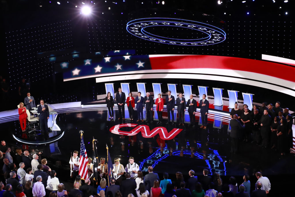 The candidates stand during the national anthem on the first night of the second 2020 Democratic U.S. presidential debate ...