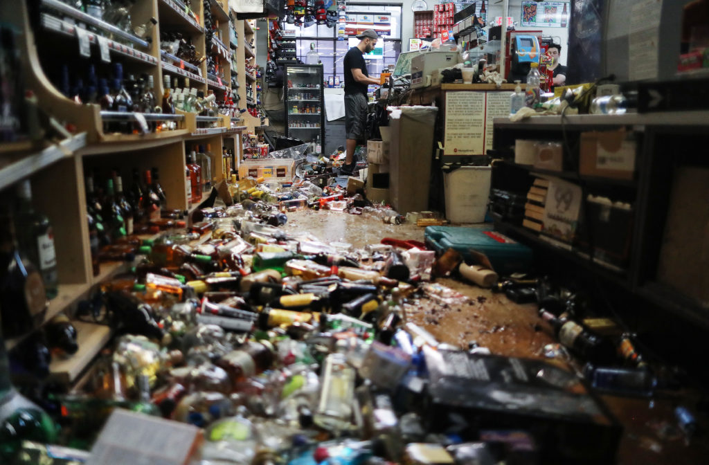 An employee works at the cash register at Eastridge Market, near broken bottles scattered on the floor, following a 7.1 magnitude earthquake which struck in the area, on July 6, 2019 in Ridgecrest, California. The earthquake, which occurred July 5th, was the second large earthquake to hit the area in two days and the largest in Southern California in 20 years. The store has remained open since the 7.1 earthquake struck in an effort to serve the community. Photo by Mario Tama/Getty Images