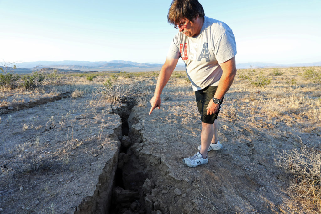 A man looks into a fissure that opened in the desert during a powerful earthquake that struck Southern California, near the city of Ridgecrest, California, U.S., July 4, 2019. Photo by REUTERS/David McNew