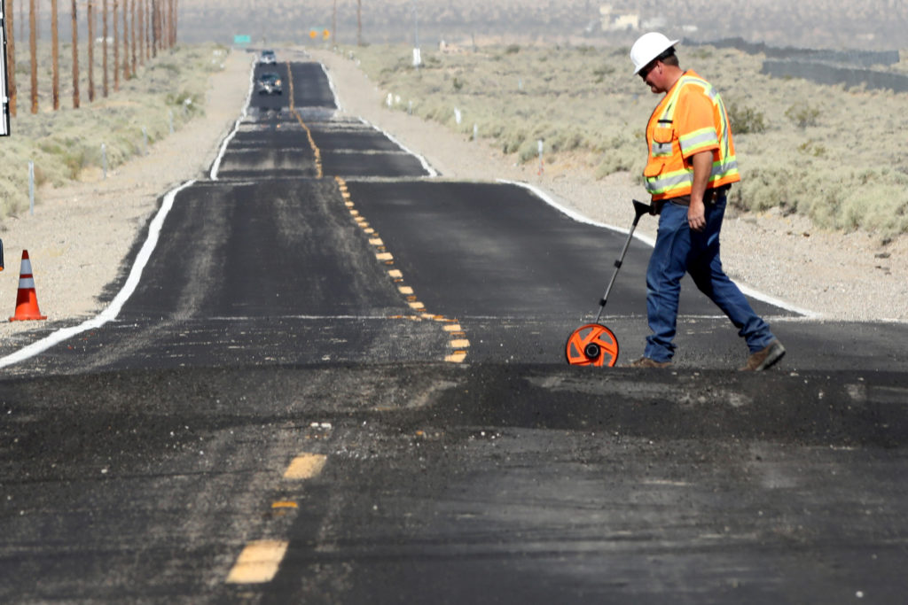 A worker takes measurements at a site where Highway 178 is distorted over newly ruptured ground after an earthquake broke, triggered by a previous day quake, in Southern California, east of the city of Ridgecrest, California, U.S., July 6, 2019.  Photo by REUTERS/David McNew