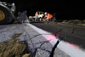 Highway workers repair a hole that opened in the road as a result of the July 5, 2019 earthquake, near Ridgecrest, California about 150 miles (241km) north of Los Angeles, early in the morning on July 6, 2019. - Southern California was hit by its largest earthquake in two decades on July 5, a 7.1-magnitude tremor that rattled residents who were already reeling from another strong quake a day earlier. Photo by Robyn Beck / AFP / Getty Images
