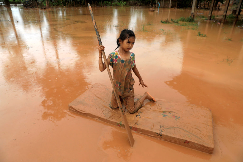 A girl uses a mattress as a raft during the flood after the Xepian-Xe Nam Noy hydropower dam collapsed in Attapeu province, Laos July 26, 2018. Picture taken July 26, 2018. Photo by REUTERS/Soe Zeya Tun