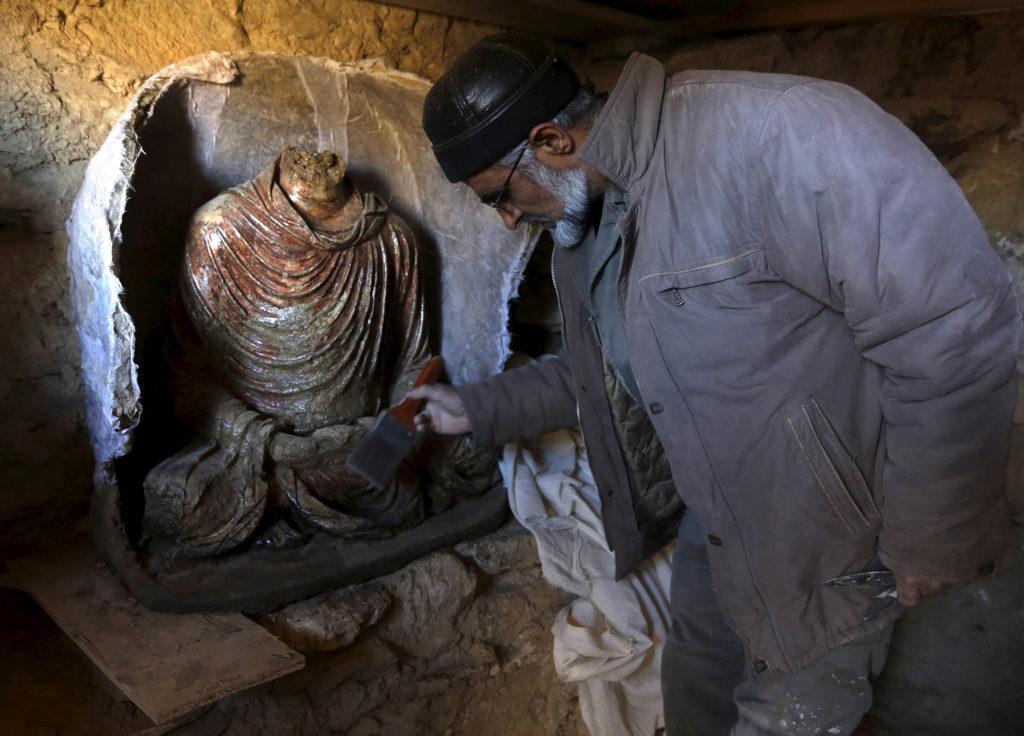 FILE PHOTO: An Afghan archeologist cleans a headless Buddha statue …
