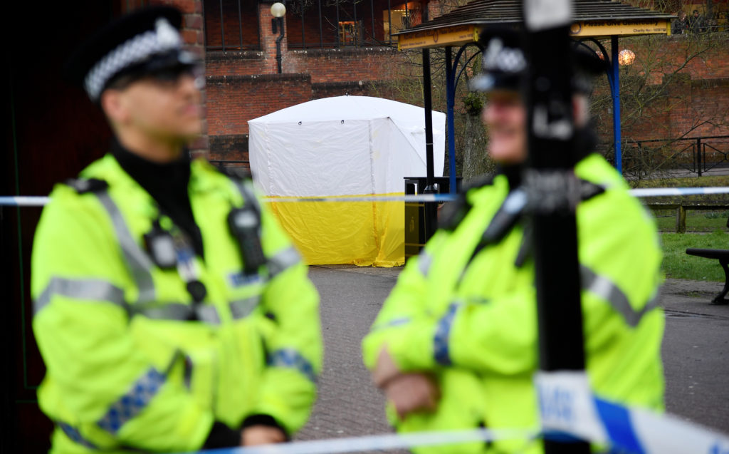 Police officers stand at crime scene tape, as a tent covers a park bench on which former Russian inteligence officer Sergei Skripal, and a woman were found unconscious after they had been exposed to an unknown substance, in Salisbury, Britain, March 6, 2018. Photo by Toby Melville/Reuters