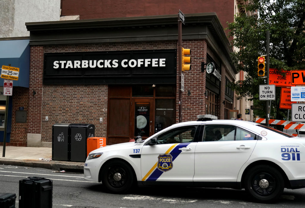A police officer drives past the center city Starbucks, where two b…