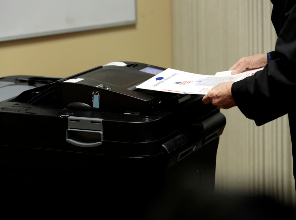 A person places his ballot in a tabulating machine as they vote in midterm election at the St. Paul Lutheran Church in East Lansing, Michigan, on November 6, 2018. Photo by Jeff Kowalsky/Reuters