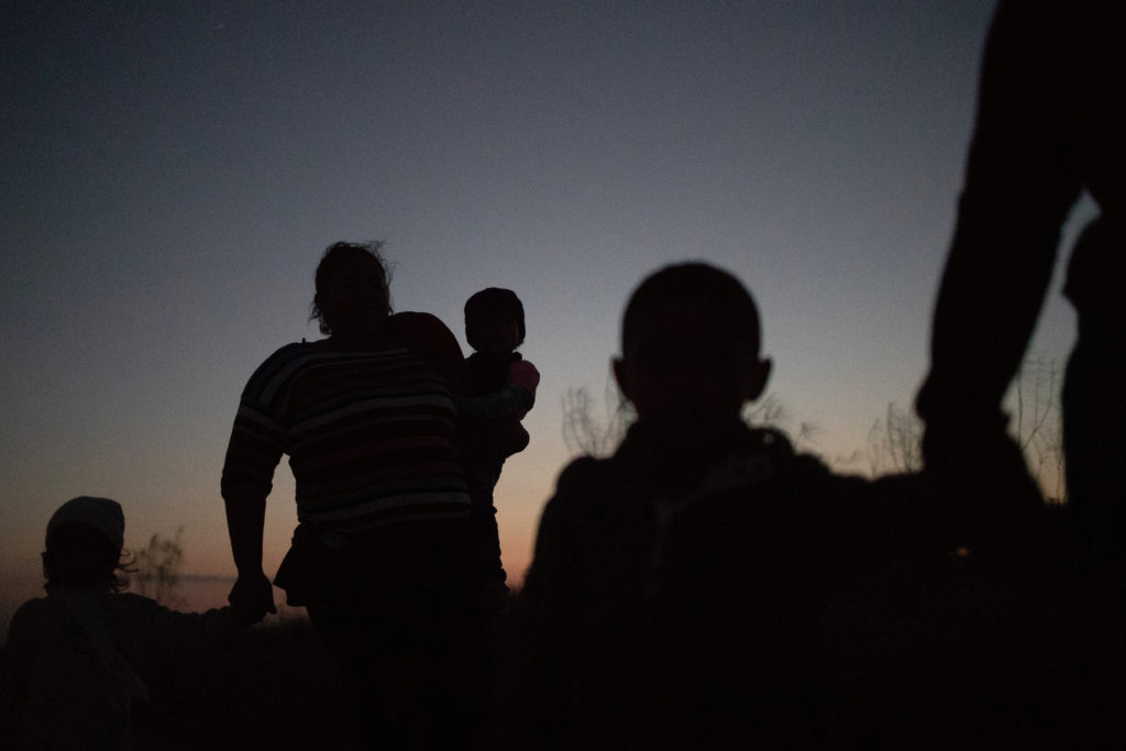 Migrants from Central America hold their children as they walk through a field after illegally crossing the Rio Grande river into the United States from Mexico in Penitas, Texas, November 7, 2018. Photo by Adrees Latif/Reuters