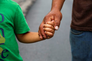 A Honduran migrant holds hands with his son as they walk along a road during his journey towards the United States, in Esquipulas, Guatemala, April 11, 2019. Photo by Luis Echeverria/Reuters