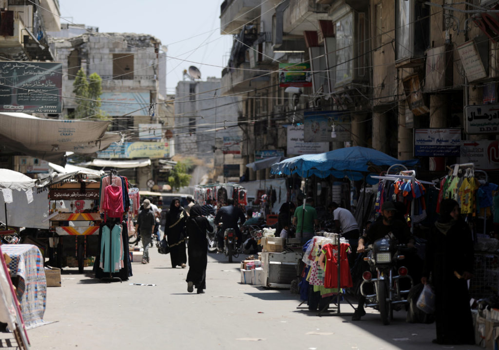 People walk past shops at a souk in the city of Idlib, Syria May 28, 2019. Photo by: Khalil Ashawi/Reuters