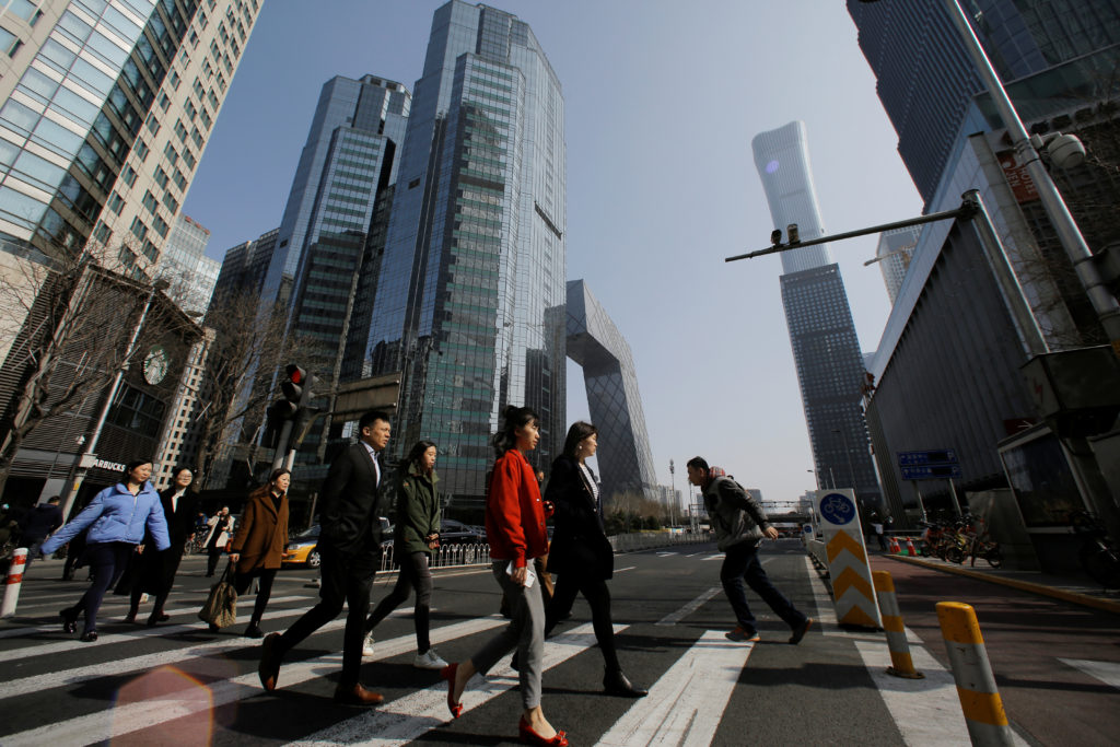 People cross a street in the Central Business District (CBD) one day before the opening session of the National People's Congress (NPC) in Beijing, China on March 4, 2019. Photo by Thomas Peter/Reuters