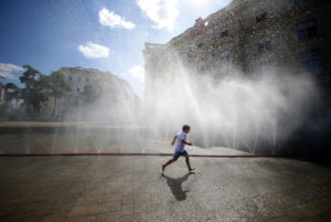 A child runs under water sprinklers during a heat wave in Vienna, Austria on July 23, 2019. Photo by Lisi Niesner/Reuters