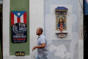 "A man walks past a sign that reads ""You are finally leaving. Ricky resign. Thanks Puerto Rico for resisting"" on the street that leads to La Fortaleza, the official residence of the Governor of Puerto Rico, and where protests calling for the resignation of Puerto Rican Governor Ricardo Rossello occurred, in Old San Juan, Puerto Rico. Photo by Marco Bello/Reuters"