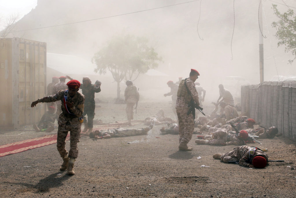 Soldiers lie on the ground after a missile attack on a military par…