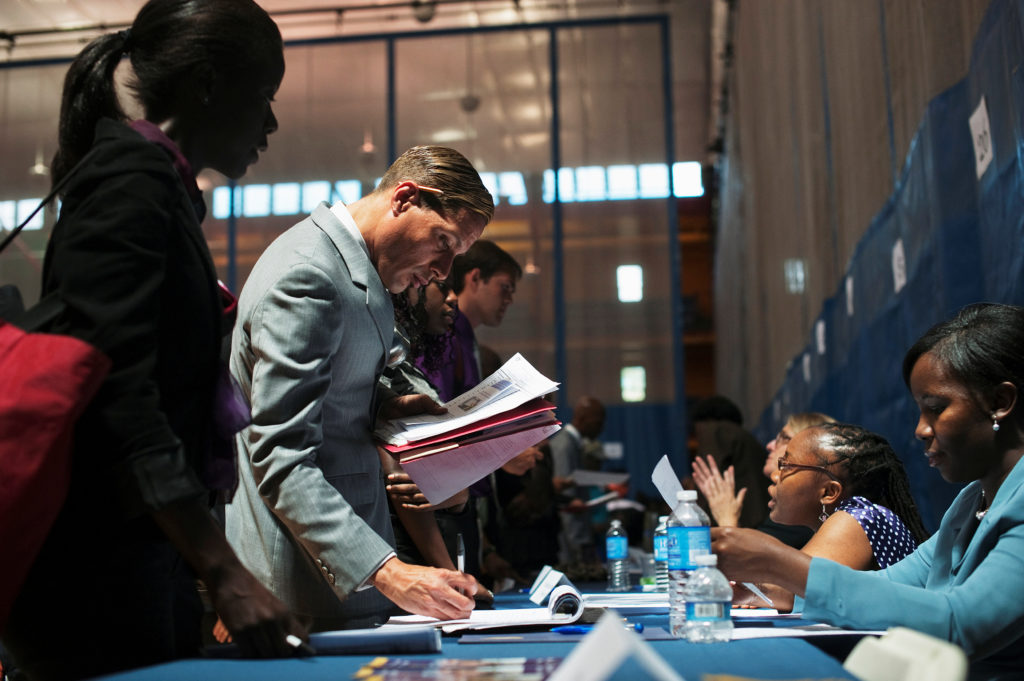 FILE PHOTO: Job seekers speak to recruiters at a job fair sponsored…
