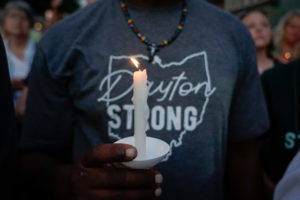 A mourner holds a candle during a vigil at scene of a mass shooting in Dayton, Ohio. Photo by Bryan Woolston/Reuters
