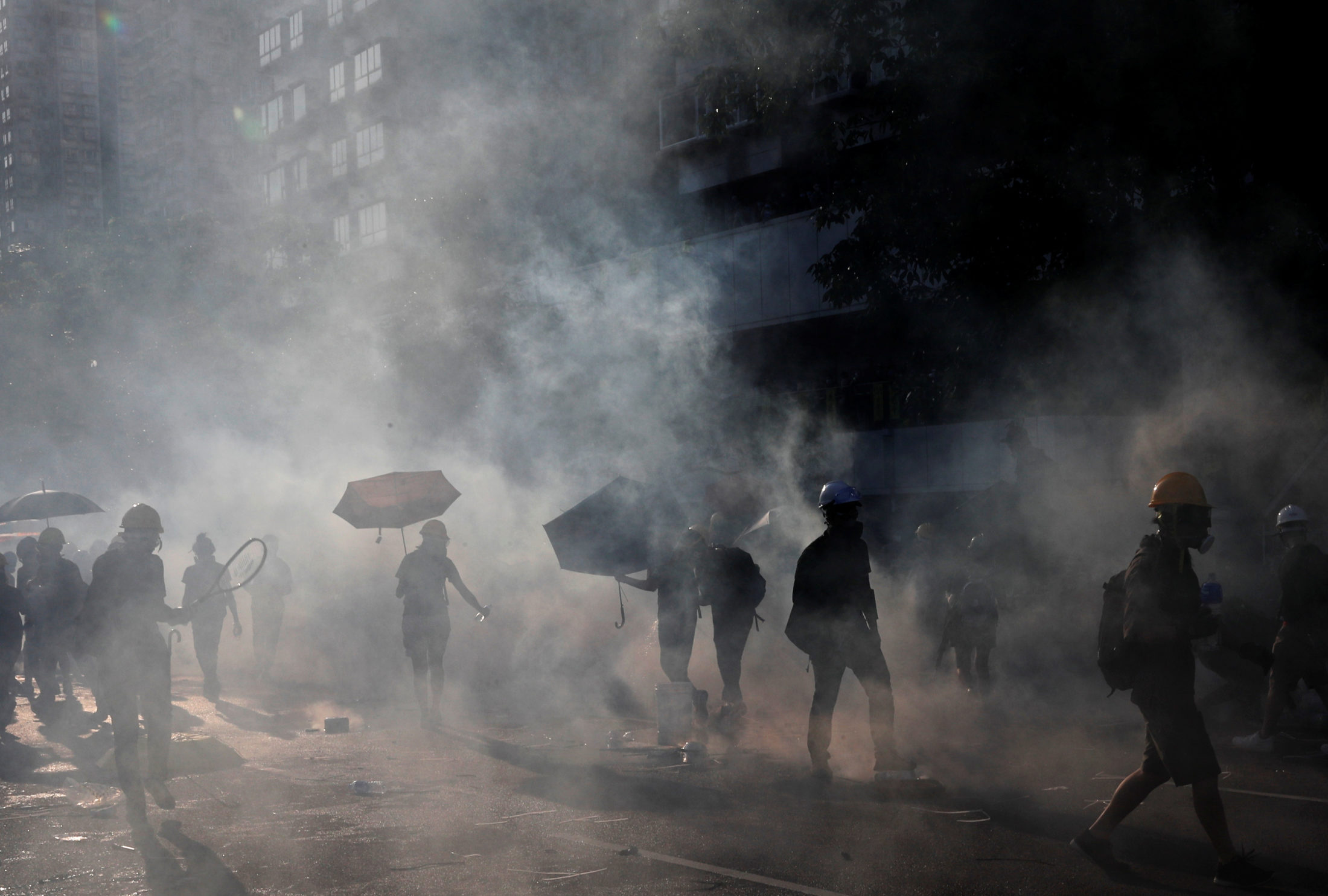 Protesters react after tear gas was fired by the police during a demonstration in support of the city-wide strike and to call for democratic reforms at Tai Po residential area in Hong Kong, China. Photo by Tyrone Siu/Reuters