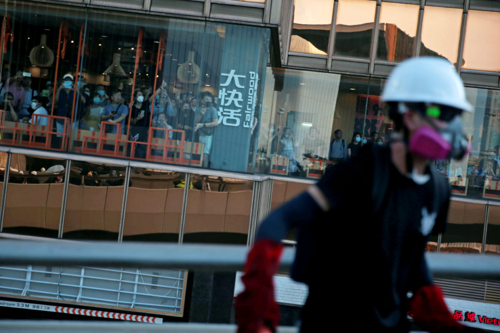 Restaurant customers watch from a window as demonstrators clash wit…