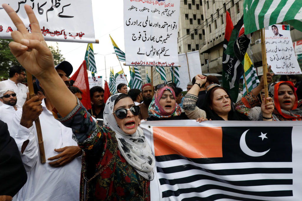 "People chant slogans as they hold the representation of Kashmir's flags during a rally expressing solidarity with the people of Kashmir, in Karachi, Pakistan August 6, 2019. The banners read ""Division of Kashmir unacceptable - U.N. and world bodies should take notice of Indian aggression in Kashmir."" Photo by Akhtar Soomro/Reuters"
