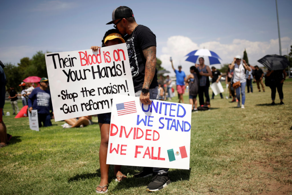 People embrace while holding placards during a rally against the visit of U.S. President Donald Trump after last weekend's shooting at a Walmart store, in El Paso, Texas, on August 7, 2019. Photo by Jose Luis Gonzalez/Reuters