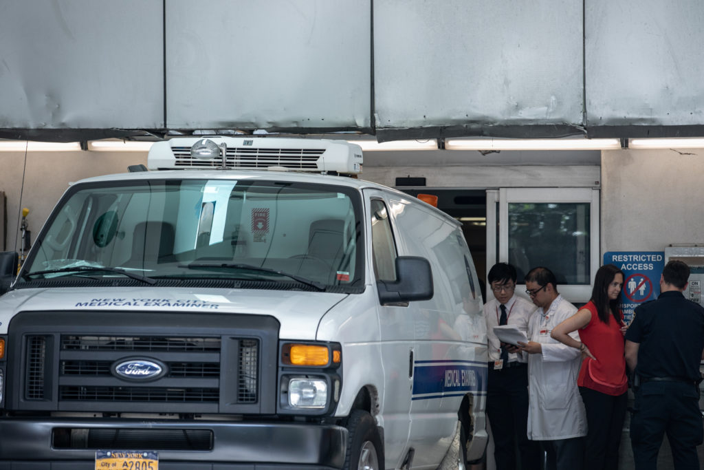 Hospital staff work on paperwork next to a medical examiner car out…