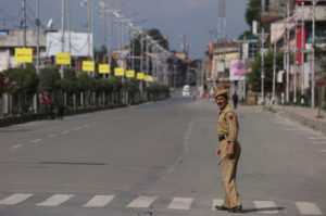 An Indian police officer crosses an empty road during restrictions on Eid-al-Adha after the scrapping of the special constitutional status for Kashmir by the Indian government, in Srinagar, August 12, 2019. Photo by Danish Ismail/Reuters