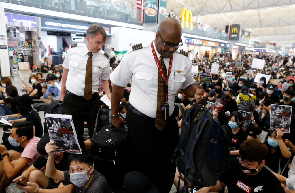 Airline crew members walk past anti-government protesters during a demonstration at Hong Kong Airport, China August 13, 2019. Photo by Thomas Peter/Reuters