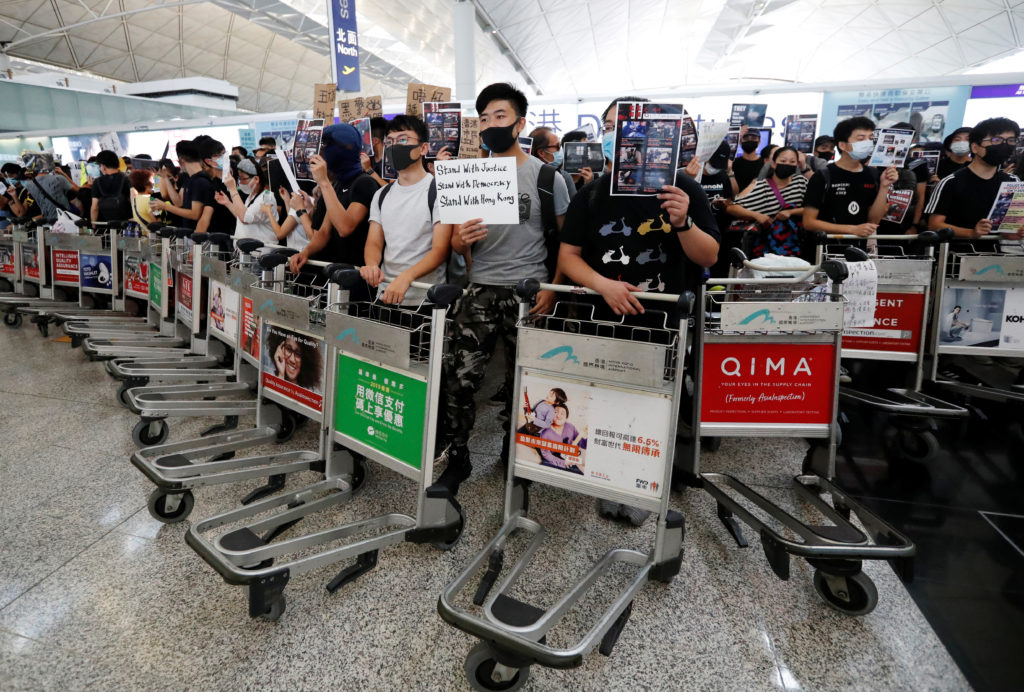 Anti-government protesters stand at a barricade made of trolleys during a demonstration at Hong Kong Airport, China on August 13, 2019. Photo by Issei Kato/Reuters