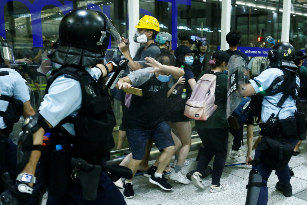 A police officer sprays pepper spray at anti-government protesters during clashes at the airport in Hong Kong, China on August 13, 2019. Photo by Thomas Peter/Reuters