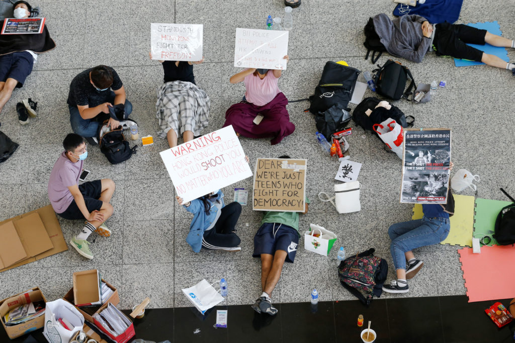 Anti-government demonstrators sit in a designated area of the arrival hall of the airport, after police and protesters clashed the previous night, in Hong Kong, China on August 14, 2019.  Photo by Thomas Peter/Reuters
