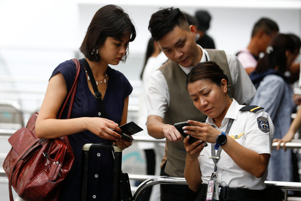 Security check people's boarding pass and travel documents at an entrance to Terminal 1 of Hong Kong Airport, China on August 14, 2019.  Photo by Thomas Peter/Reuters