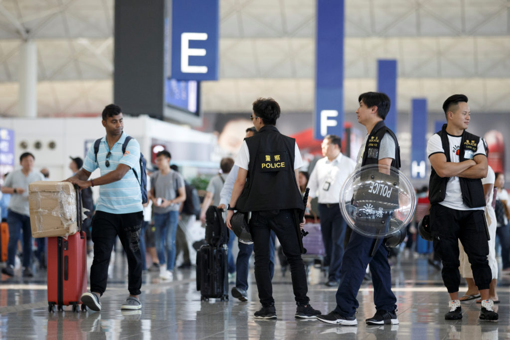 Police patrol the departure hall of the airport in Hong Kong after previous night's clashes with protesters, China on August 14, 2019. Photo by Thomas Peter/Reuters