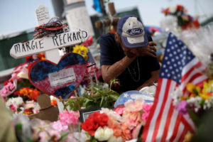 Antonio Basco, whose wife Margie Reckard was murdered during a shooting at a Walmart store, kneels next to a white wooden cross bearing the name of his late wife, at a memorial for the victims of the shooting in El Paso, Texas, on August 15, 2019. Photo by Jose Luis Gonzalez/Reuters