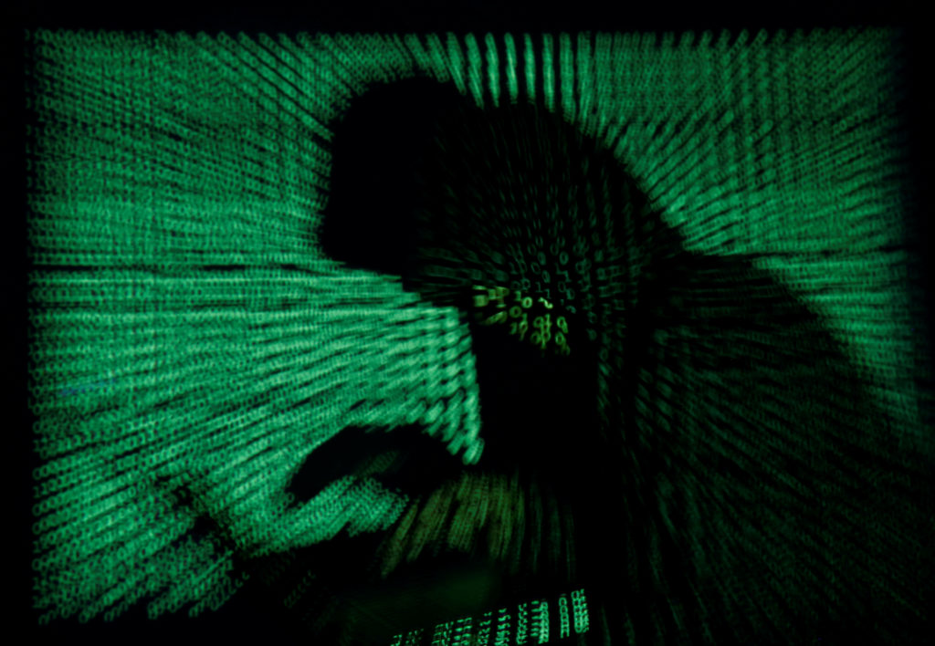A hooded man holds a laptop computer as cyber code is projected on him in this illustration picture taken on May 13, 2017. Photo by: Kacper Pempel/File Photo/Reuters