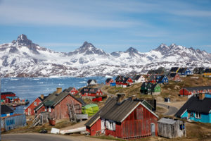 FILE PHOTO: Snow covered mountains rise above the harbour and town of Tasiilaq, Greenland, June 15, 2018. Photo by Lucas Jackson/Reuters