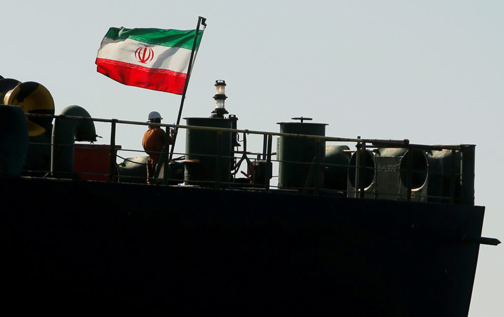 A crew member raises the Iranian flag on Iranian oil tanker Adrian Darya 1, previously named Grace 1, as it sits anchored after the Supreme Court of the British territory lifted its detention order, in the Strait of Gibraltar, Spain, on August 18, 2019. Photo by Jon Nazca/Reuters