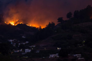 Flames and smoke from a forest fire are seen in the village of Moya on the Canary Island of Gran Canaria, Spain on August 18, 2019. Photo by Borja Suarez/Reuters