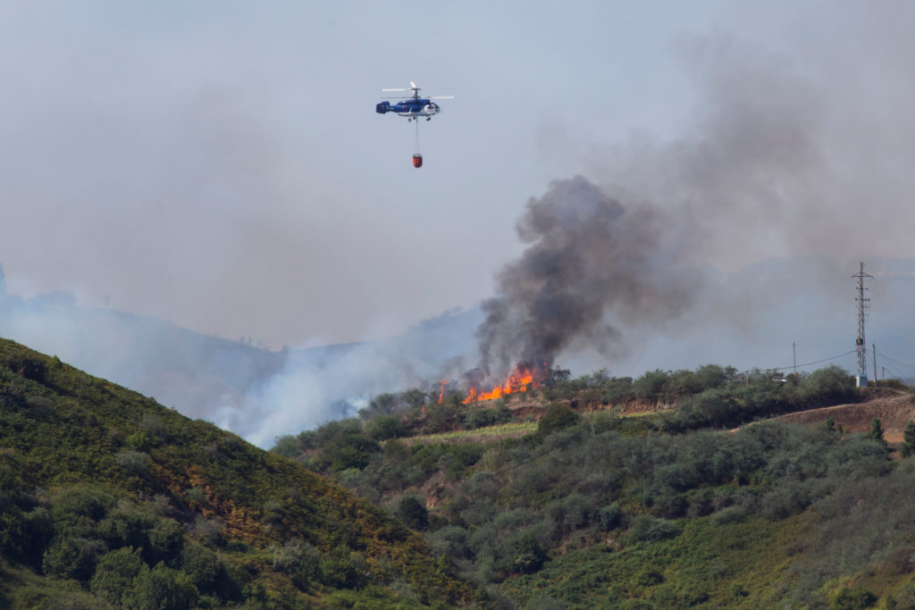 A helicopter carries water to fight a forest fire seen in the village of Guia on the Canary Island of Gran Canaria, Spain, August 19, 2019. Photo by Borja Suarez/Reuters