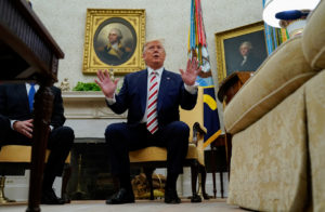 U.S. President Donald Trump answers questions from reporters while sitting in front of portraits of former U.S. presidents George Washington and Thomas Jefferson as he meets with Romania's President Klaus Iohannis in the Oval Office of the White House in Washington, on August 20, 2019. Photo by Kevin Lamarque/Reuters