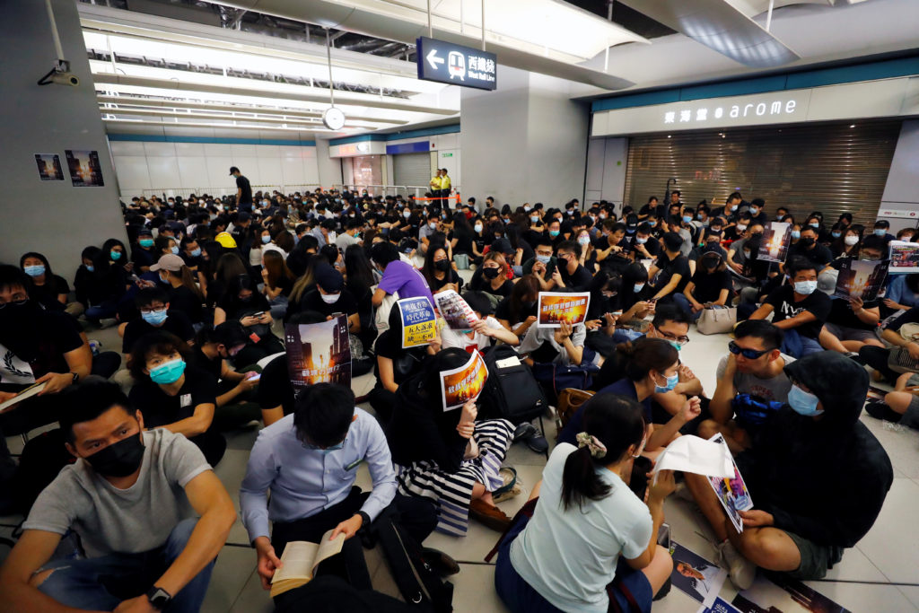 People protest during a silent sit-in gathering at Yuen Long MTR st…