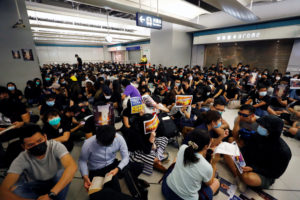 People protest during a silent sit-in gathering at Yuen Long MTR station, the scene of an attack by suspected triad gang members a month ago, in Yuen Long, New Territories, Hong Kong, China August 21, 2019. Photo by Kai Pfaffenbach/Reuters