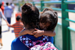 A Central American migrant carries her child just after she was sent to Mexico from the U.S. under the Migrant Protection Protocols (MPP), in Tijuana, Mexico, July 18, 2019. Under new rules proposed by the Trump administration, migrant children could be detained with their families indefinitely. Photo by Carlos Jasso/Reuters
